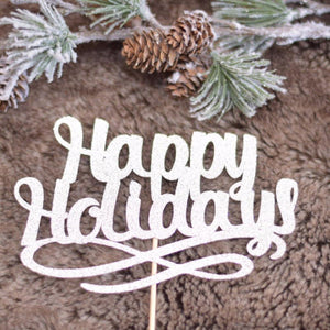 Happy Holidays silver glittery cake topper on faux fur background with pine tree branch in background