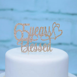 65 years blessed extra shiny glitter cake topper on white cake with blue background