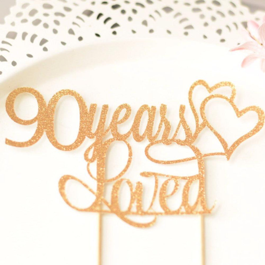 90 Years loved black sparkle cake topper with two intertwined hearts on white background