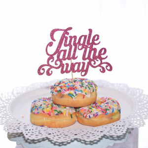 Jingle all the way pink sparkle cake topper placed in three sprinkle donuts