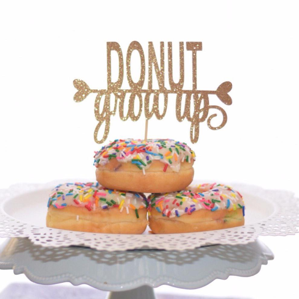 Donut Grow Up fine font gold glitter cake topper on three sprinkle donuts