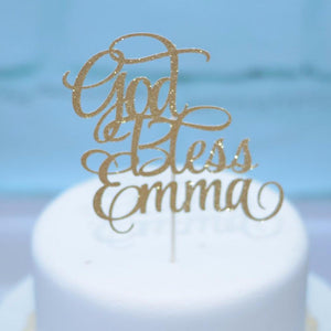 God Bless Emma gold glitter sparkle cake topper on white cake and blue background