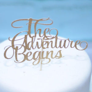 The Adventure Begins gold glitter sparkle cake topper