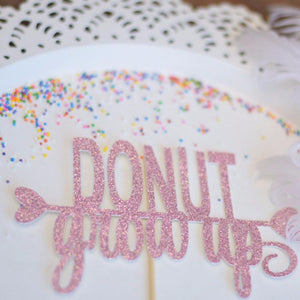 donut grow up pink sparkle glitter cake topper on white plate with sprinkles