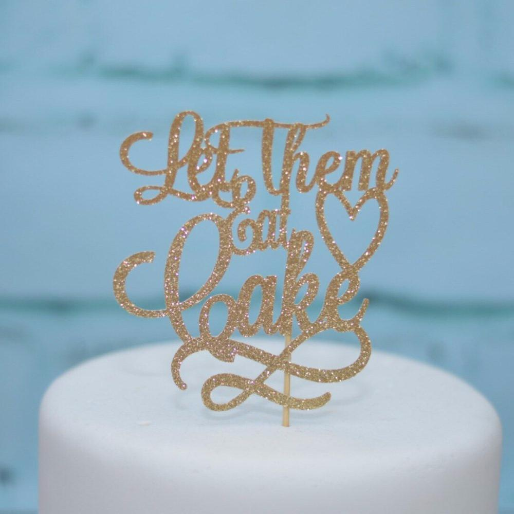 Let Them Eat Cake sparkly gold cake topper on a white cake