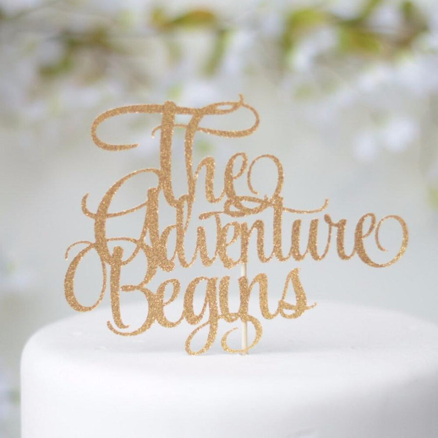 The adventure begins blue sparkle glitter cake topper on white background