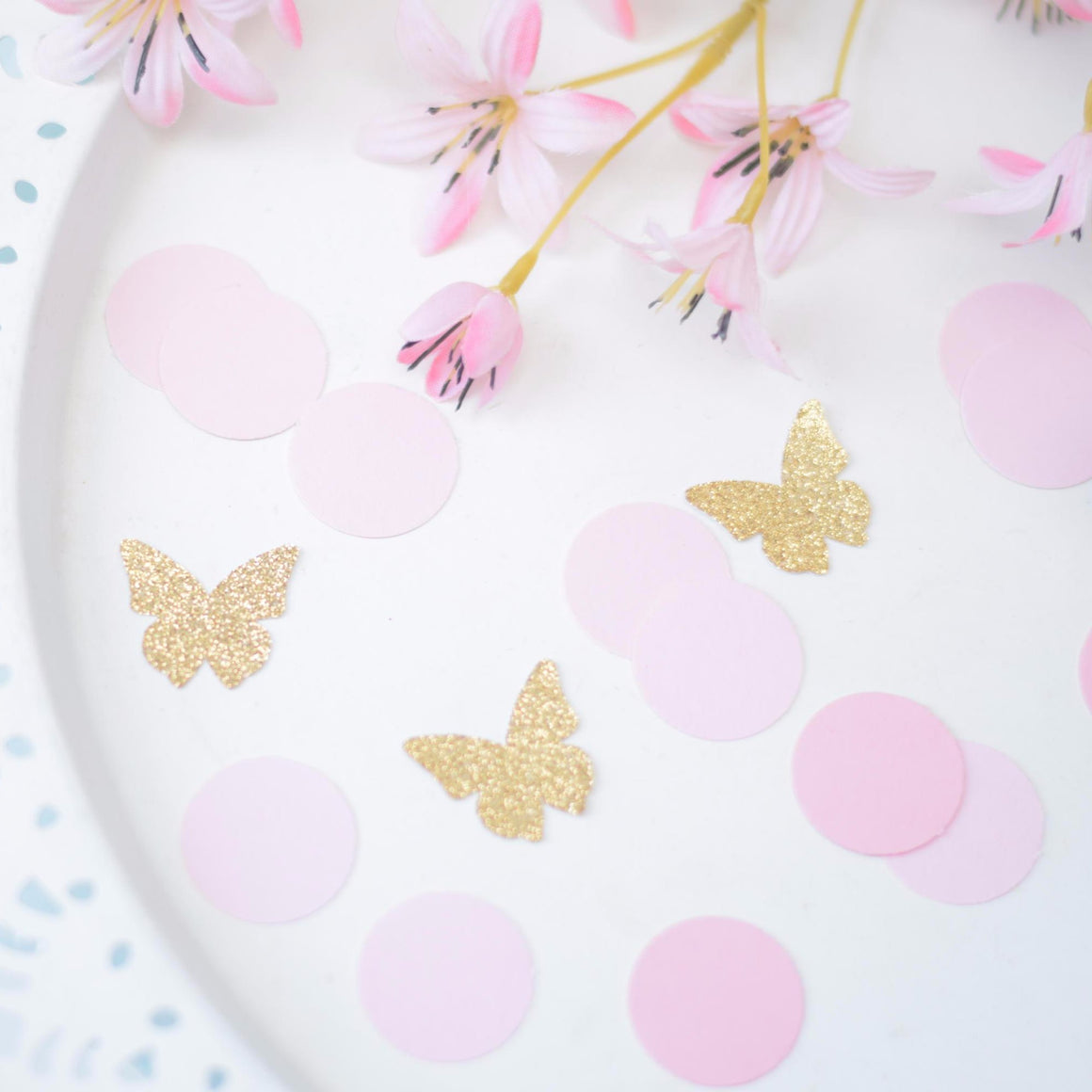 gold sparkle butterflies and pink circle confetti on white background