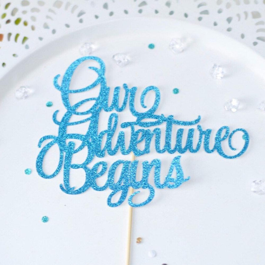 Our Adventure Begins gold sparkly cake topper on white cake