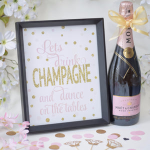 Let's Drink Champagne And Dance On The Tables image framed beside a bottle of champagne