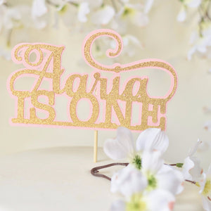 Aaria is one gold and pink cake topper