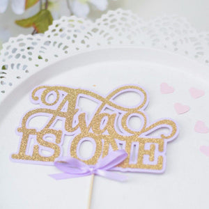 Ava is one gold glitter and sparkle cake topper with lavender bow