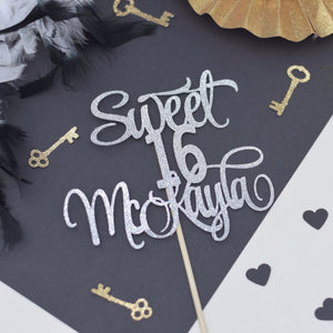 Sweet 16 McKayla silver sparkle cake topper on black background with gold keys