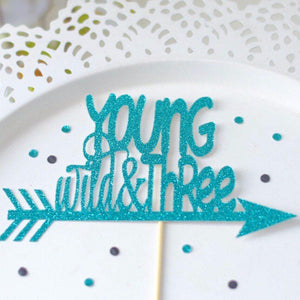 Young wild and three teal sparkle glitter cake topper on a white plate