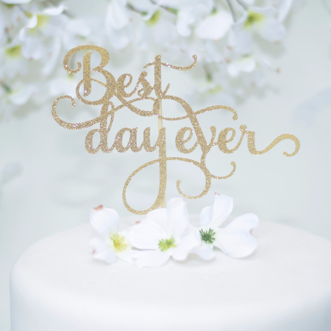 Best Day Ever gold glitter cake topper on a white cake with flower details