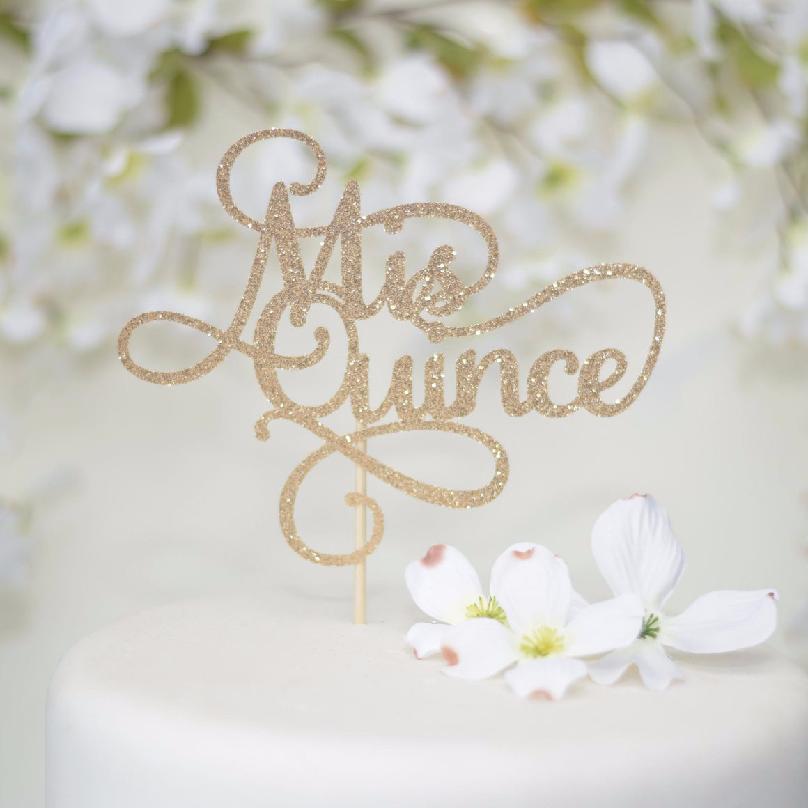 Mis Quince gold sparkle cake topper on white cake with white flowers