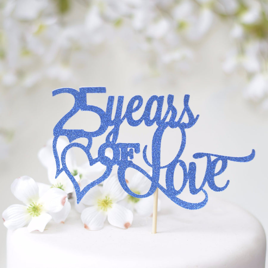 25 Year of Love with gold heart with gold sparkly font on a white cake with blue background