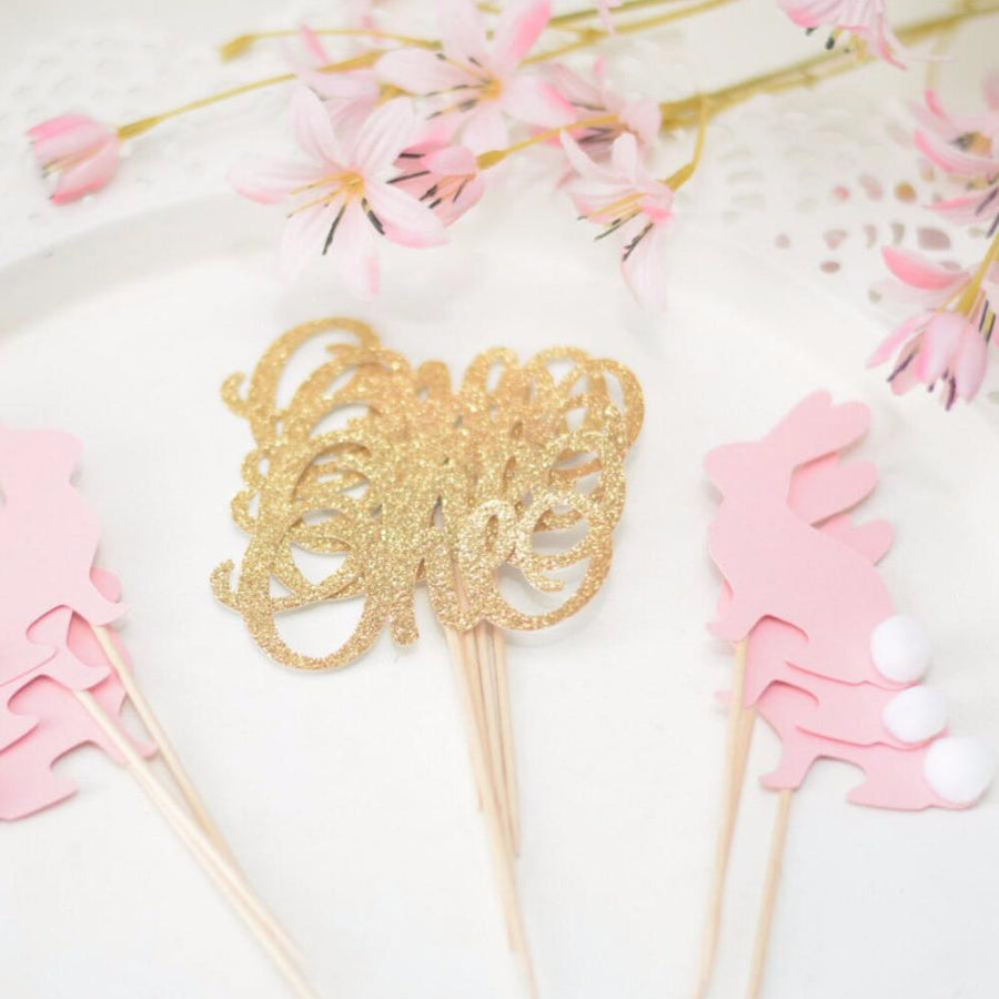 one sparkly gold cupcake toppers with pink bunny cupcake toppers on white plate with pink flowers
