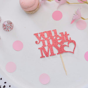 You melt my heart red sparkle cupcake topper on a white plate with pink confetti