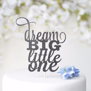 Dream big little one black glitter cake topper on white cake with blue flower