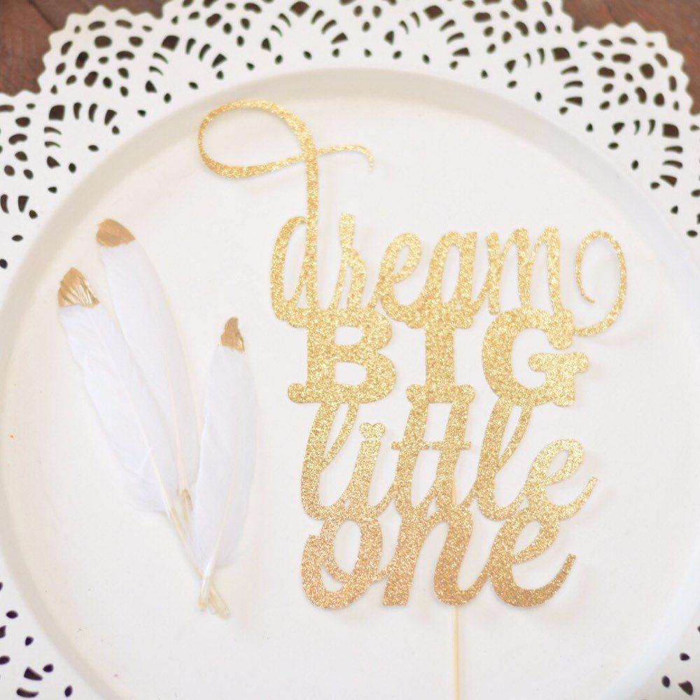 Dream big little one gold sparkle and glitter cake topper on white plate with gold dipped feathers