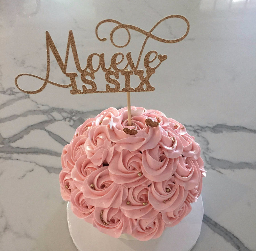 Maeve is six gold sparkle cake topper with delicate details
