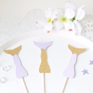 gold and silver mermaid cupcake toppers on white plate