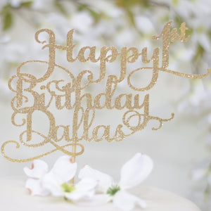 Happy 1st Birthday Dallas gold glitter cake topper on white cake with flower background