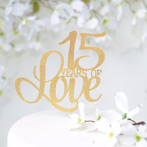 15 Years of Love gold glitter cake topper on a beautiful white cake with floral background