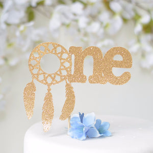 One gold glitter cake topper with dream catcher details, three feathers on a white cake with blue flowers