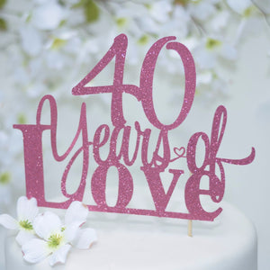40 years of love pink glittery sparkle cake topper on white cake