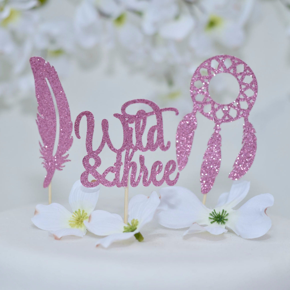 Wild & Three pink sparkle cupcake topper with feather and dream catcher cupcake toppers on a white cake