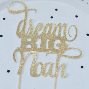 Dream big Noah gold sparkle glitter cake topper on white background with black jewels