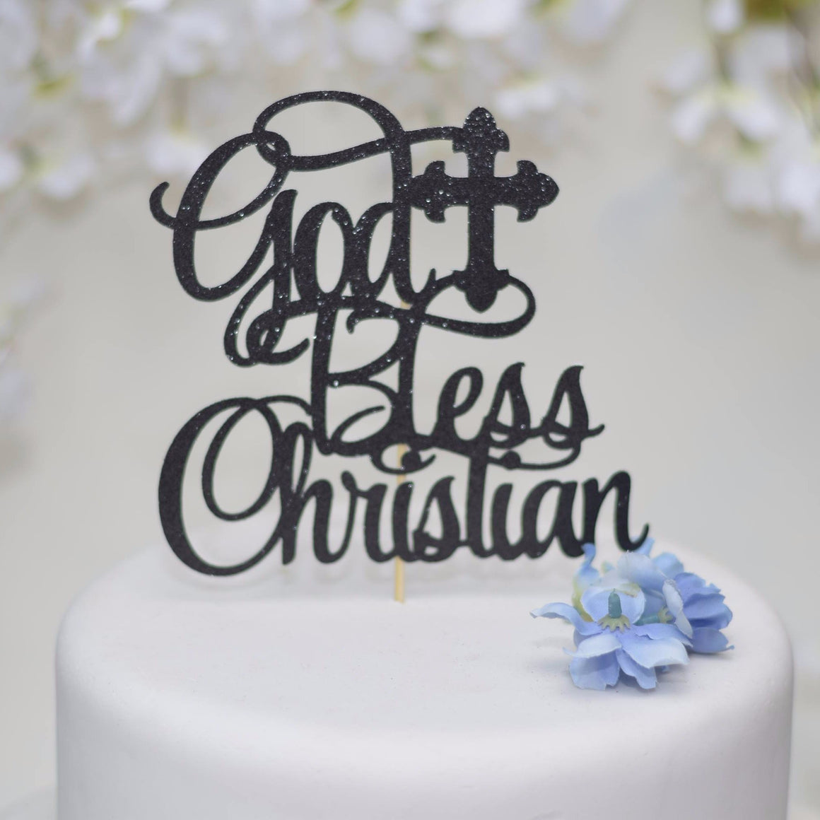 God bless Christian black sparkle glitter cake topper on white cake with blue flower