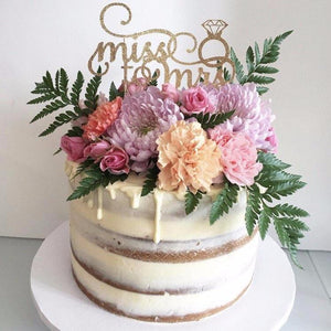 miss to mrs gold glitter cake topper with diamond ring details on a white cake with floral details