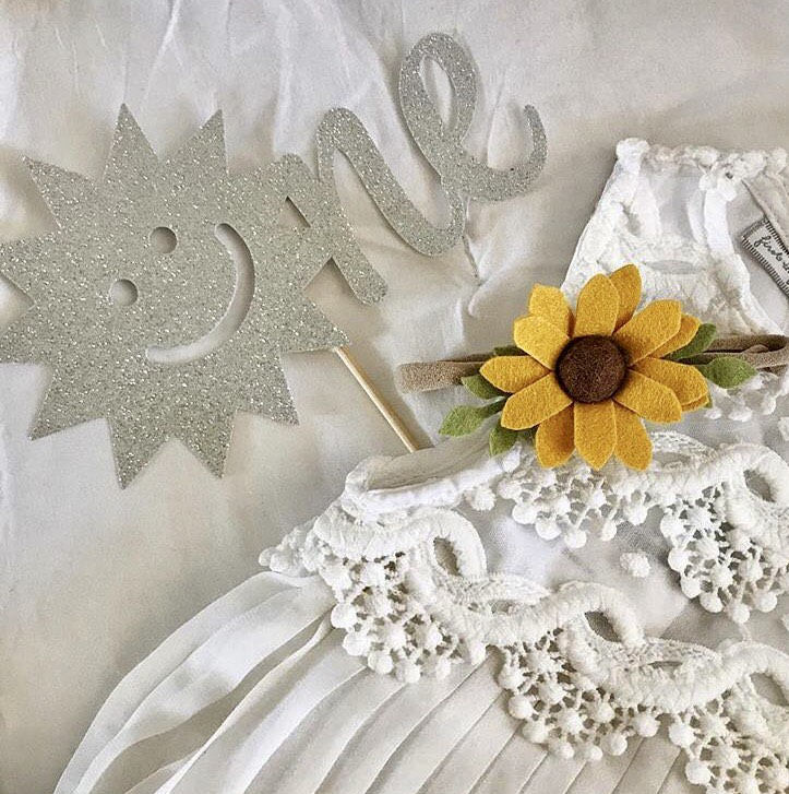 One sunshine cake topper in gold glitter sparkles on a white cake