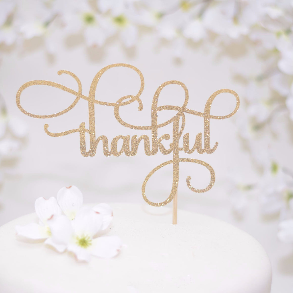 Thankful gold glitter cake topper on white cake