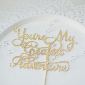 You're my Greatest Adventure gold glitter sparkle cake topper on white plate