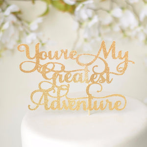 You're my greatest adventure gold sparkle cake topper on a white cake with a floral background