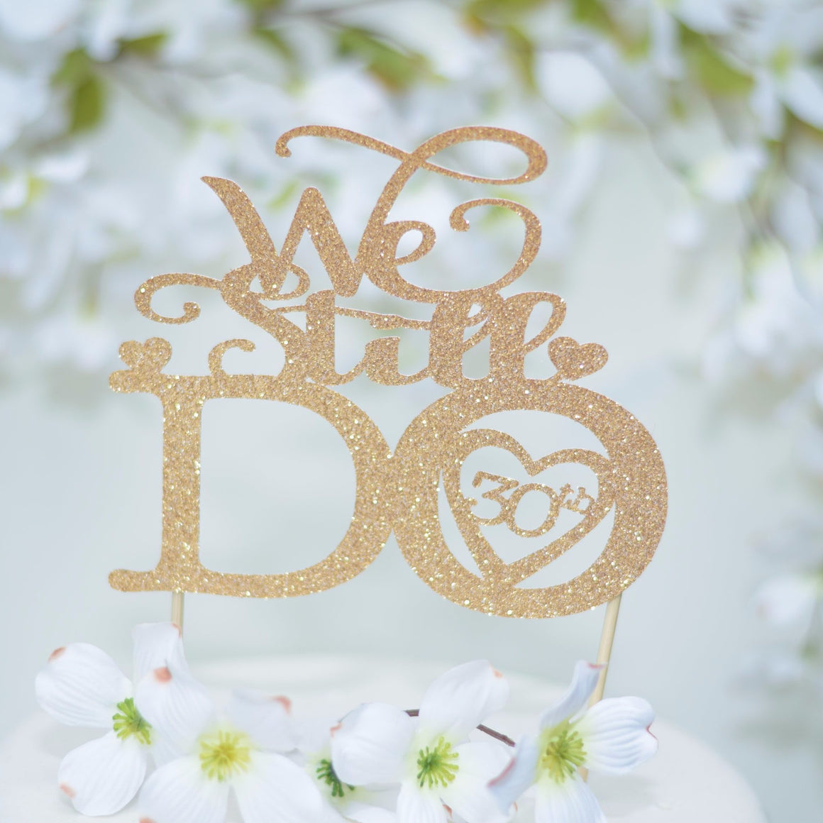 We Still Do 30th Anniversary Cake Topper in Gold Glitter font on a white wedding cake with floral background