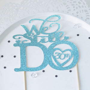 We Still Do 30th Wedding Anniversary cake topper on white background in light blue glitter font