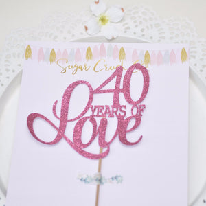 40 years of love pink cake topper on white plate