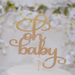 Oh Baby gold sparkle glitter cake topper on white cake with floral background