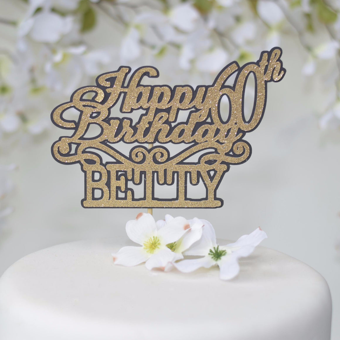 Happy 60th Birthday Betty gold sparkle cake topper with black outline on a white cake