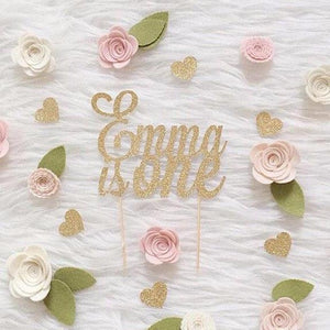 Emma is one gold glitter cake topper on white background wit pink and green felt flower details