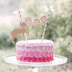 unicorn cake topper on pink cake