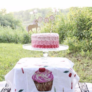 Unicorn cake setup on cupcake tablecloth outside