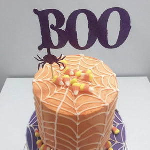 Boo black spider cake topper on orange and purple spiderweb cake