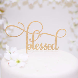 Elegant Blessed gold glitter cake topper on a white cake with floral details