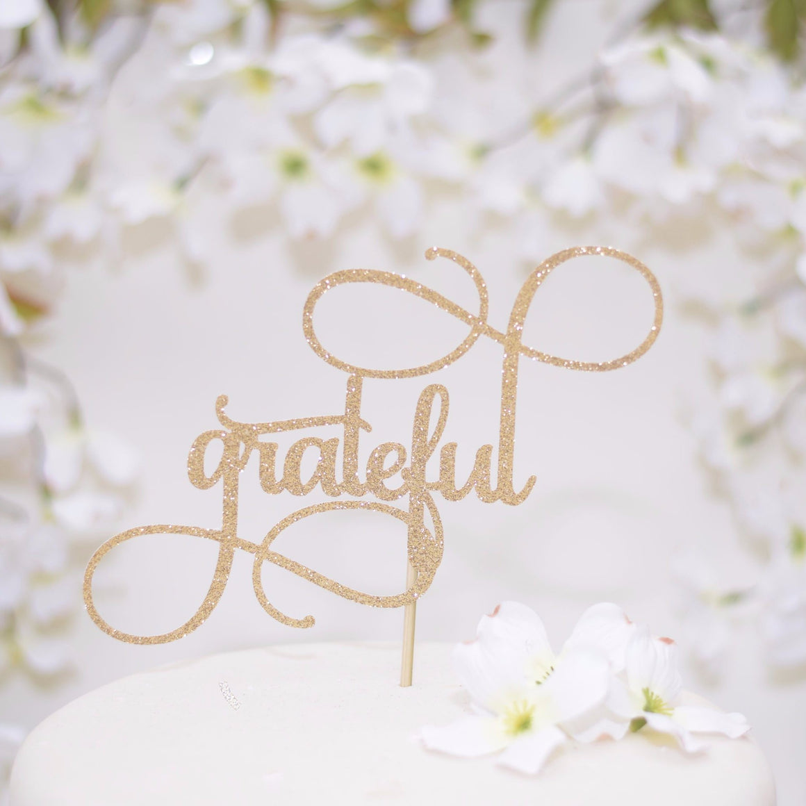 grateful gold sparkle glitter cake topper on elegant white wedding cake with floral background