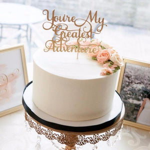 You're my greatest adventure gold glitter cake topper on white wedding cake with a photo of a couple in the background